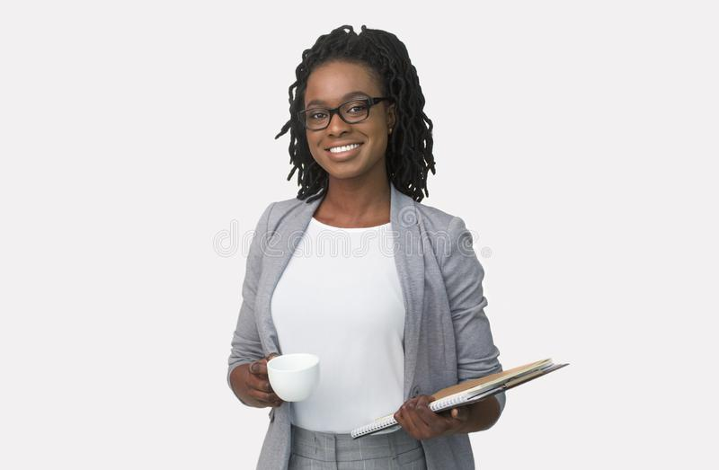 Positive Afro Businesswoman Holding Folders And Coffee Cup, White Background. Positive African American Businesswoman Holding Folders And Coffee Cup On White stock photography