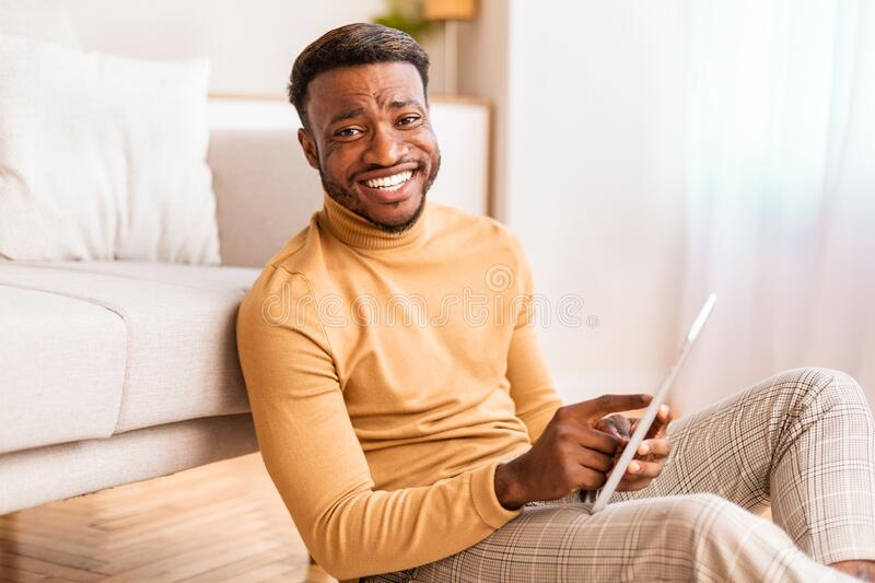 Afro Man Using Tablet Smiling Sitting On Floor At Home stock photo