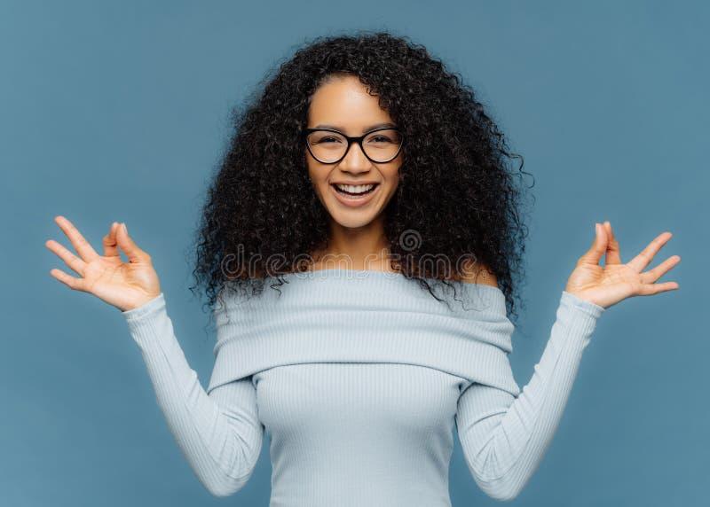 Positive Afroamerikanerdame macht O.K.geste mit beiden Händen, meditiert Innen, trägt moderne Strickjacke und Eyewear und ist stockbild