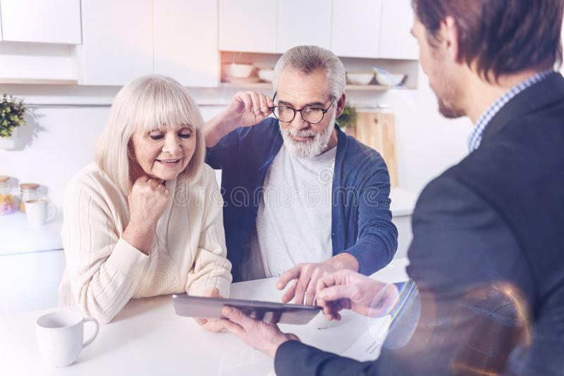 Positive aged couple meeting with their real estate agent. Just have a look. Positive elderly couple looking at the screen of tablet while talking with their royalty free stock image