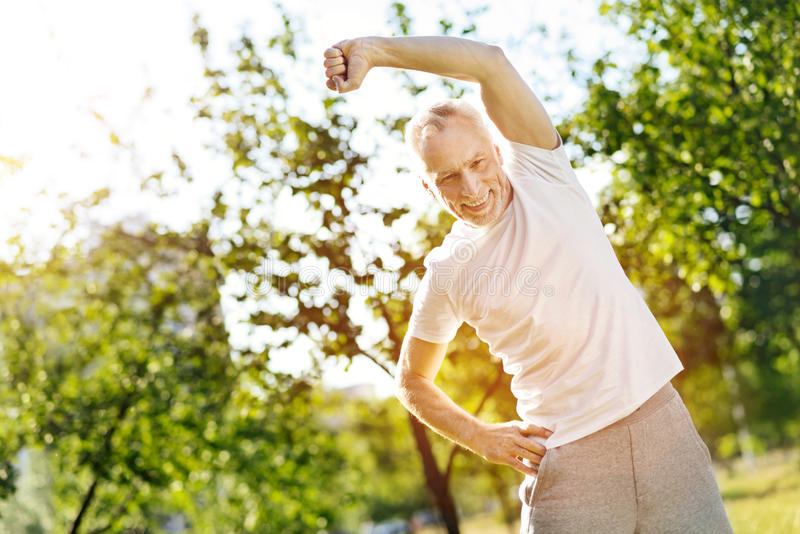 Positive aged man doing stretching exercises royalty free stock photo