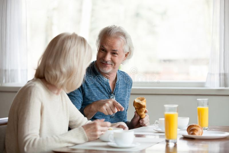 Positive aged spouses eating breakfast talking sitting in the kitchen royalty free stock images