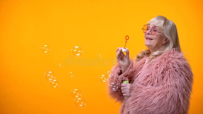 Positive aged woman in funny pink coat and round sunglasses making soap bubbles royalty free stock images