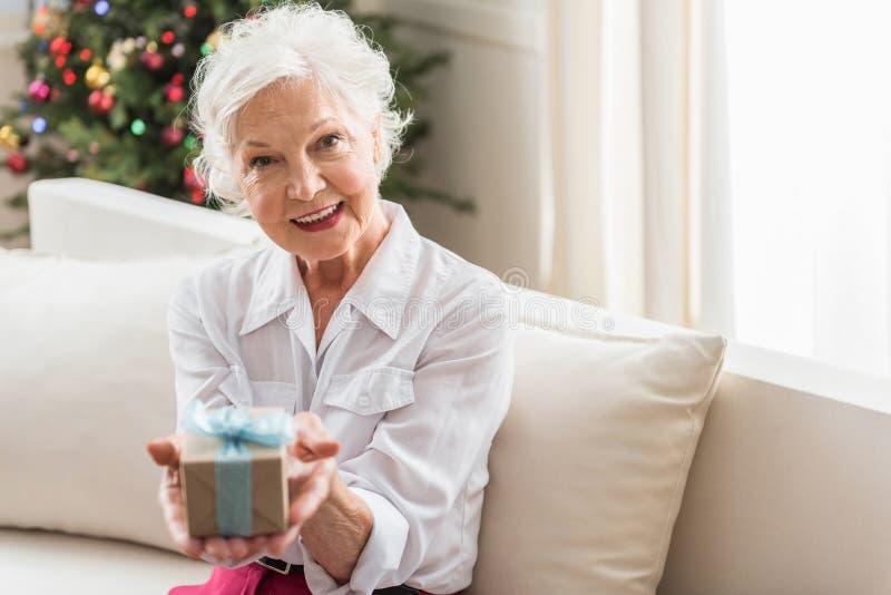 Positive alte Dame steht auf Sofa still stockfotos