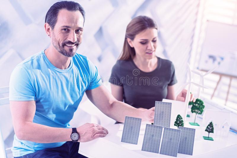 Positive architect sitting at the table and working with solar batteries stock photo