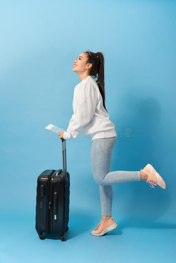 Positive asian female pictured isolated on background with suitcase and tickets for plane dancing with joy of upcoming journey royalty free stock photos