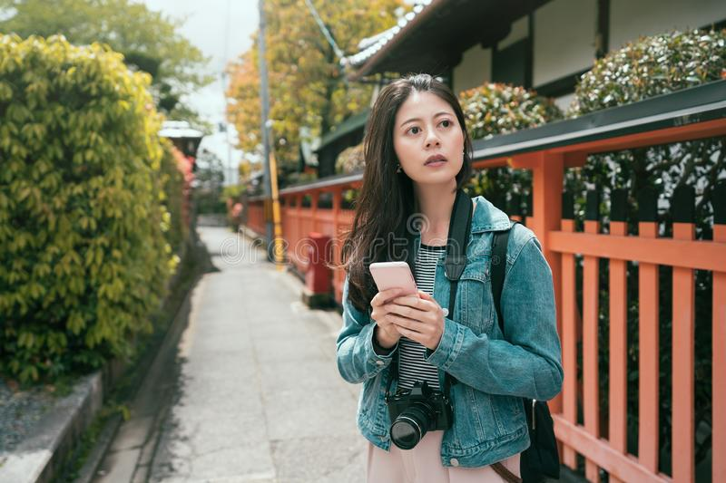 Positive asian girl traveler using smartphone royalty free stock image