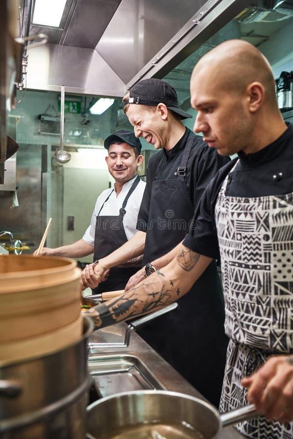 Positive Atmosphäre Vertikales Foto des Chefs und seine lächelnden Assistenten, die zusammen Nahrung in einer Küche zubereiten lizenzfreie stockbilder