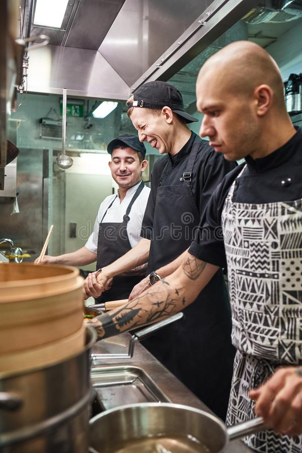 Positive atmosphere. Vertical photo of chef and his smiling assistants preparing food together in a kitchen. royalty free stock images