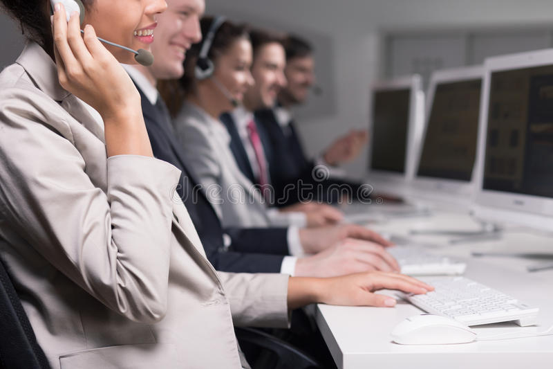 Positive attitude is crucial for their job. Cropped picture of smiling consultants royalty free stock images