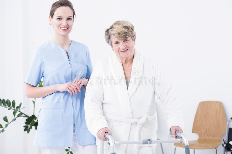 Positive attitude is important during recovery. Senior women with walking zimmer and smiling carer, standing in light interior stock photography