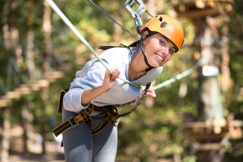Positive attractive woman leaning forwards. Look at me. Pleasant delighted well built woman leaning forwards and smiling while doing adventure climbing royalty free stock images