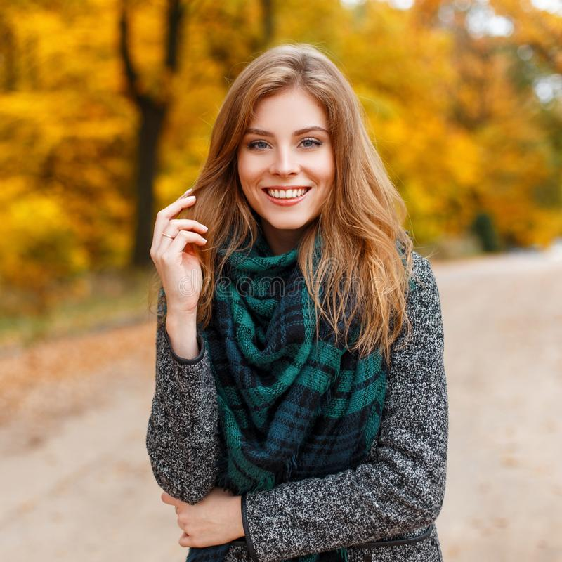 Positive attractive young woman in a warm gray fashionable modern outerwear with a green scarf in the park. Cheerful girl model. On the background of yellow royalty free stock photos