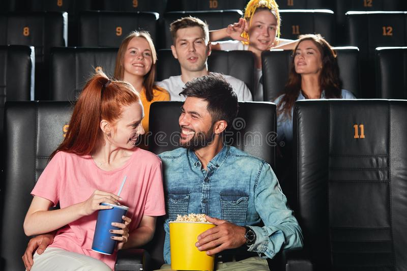 Positive awesome man telling jokes to his girlfriend. Positive awesome men telling jokes to his girlfriend, entertaining her at the cinema. close up photo royalty free stock photo