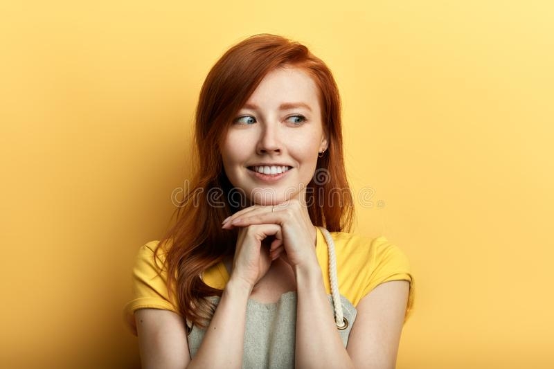 Positive awesome young woman in apron falls in love stock photo
