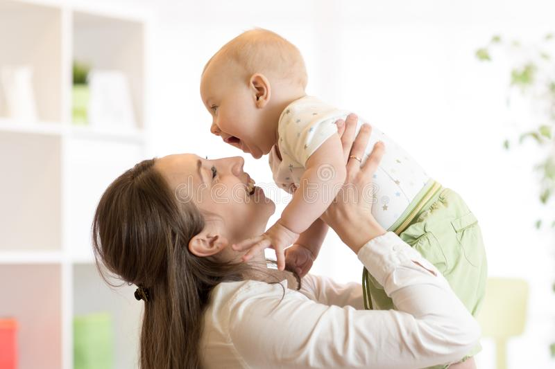 Positive baby and mom. Young mother plays with her little son. royalty free stock image