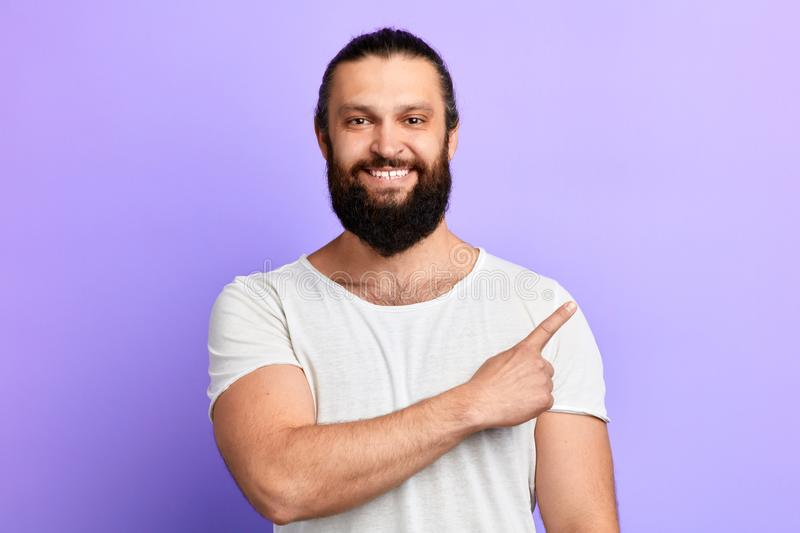 Positive bearded guy pointing aside with finger . stock photos