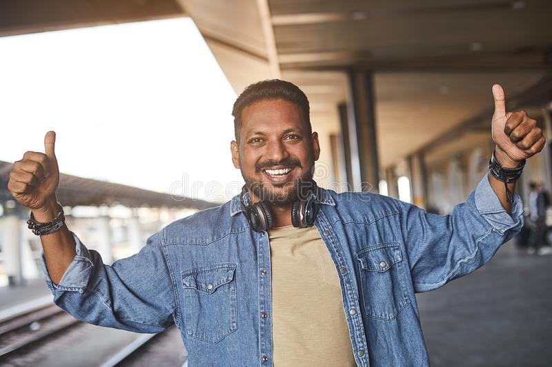 Overjoyed hindu man thumbing up on the platform. Positive bearded hindu man standing on the railway platform while thumbing royalty free stock photos