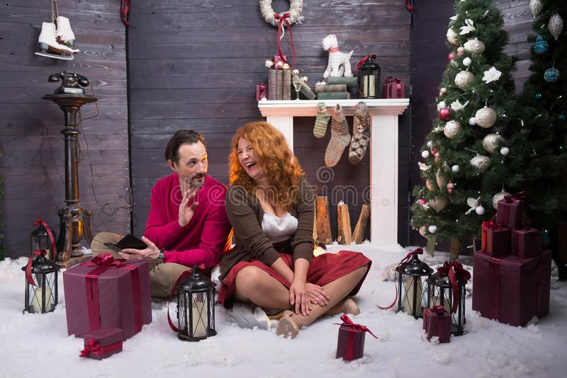 Positive bearded husband entertaining his charming wife during New Year holidays royalty free stock image