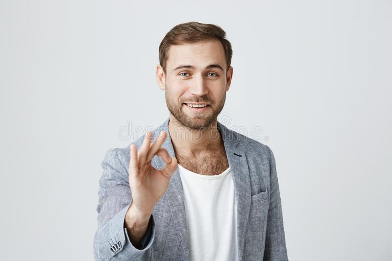 Positive bearded male wears trendy clothes makes ok gesture and smiles at camera, has happy expression, against stock photos