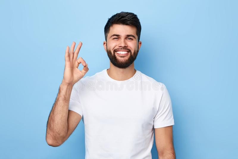 Positive bearded man in white T-shirt showing ok sign stock photography