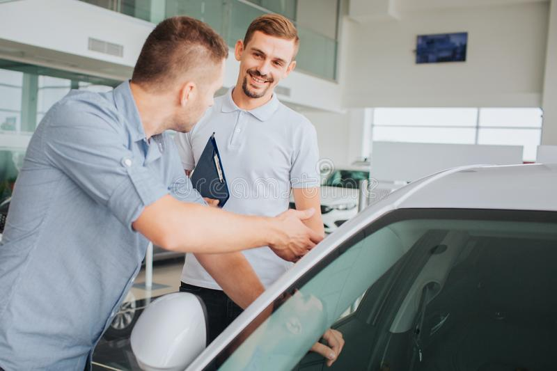Positive and bearded young seller stand in front of customer and looks at him. He is smiling. Buyer touches car and stock photo