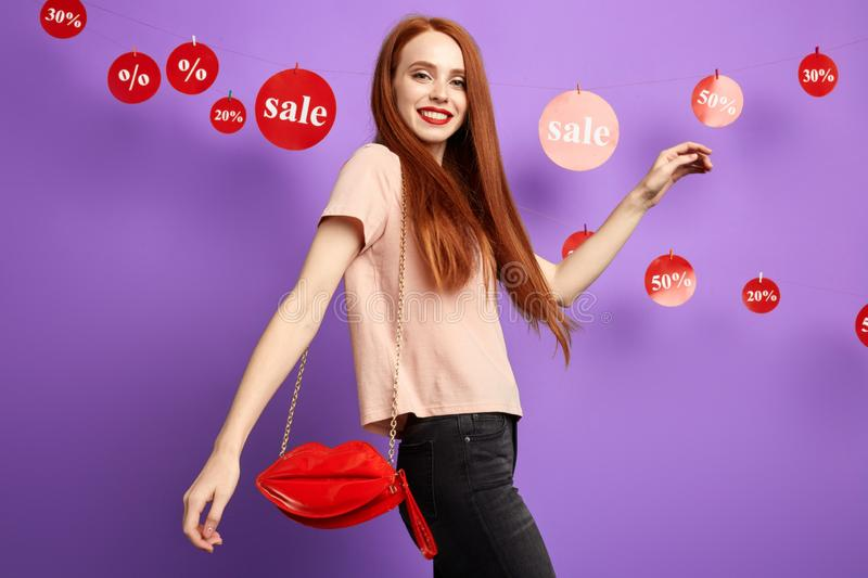 Positive beautiful charming woman is walking in the shopping mall royalty free stock photos
