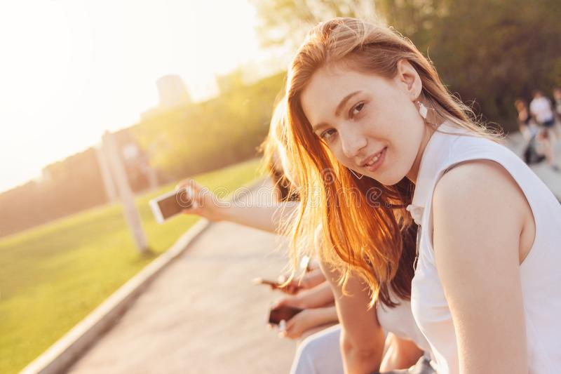 Positive beautiful happy red haired girl with friends on city street background, summer sunset time stock images