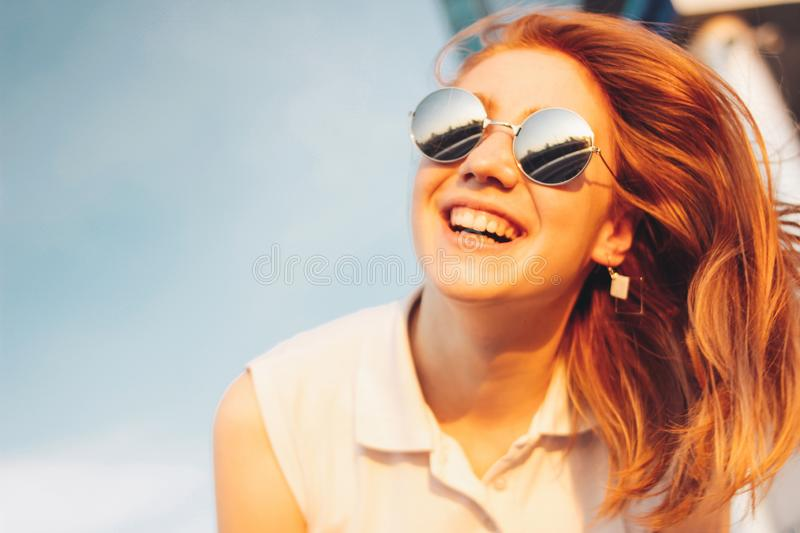 Positive beautiful happy red haired girl in the mirror sunglasses on blue sky background, summer sunset time stock photo