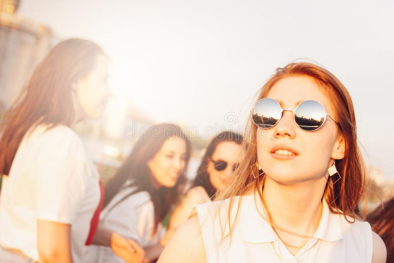 Positive beautiful happy red haired girl in the mirror sunglasses with friends on blue sky background, summer sunset time royalty free stock photography