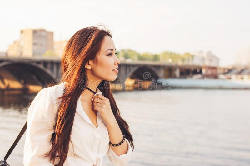 Positive beautiful long hair happy asian girl in white shirt on city river bridge background, summer travel vacation time. Positive beautiful long hair happy royalty free stock photography