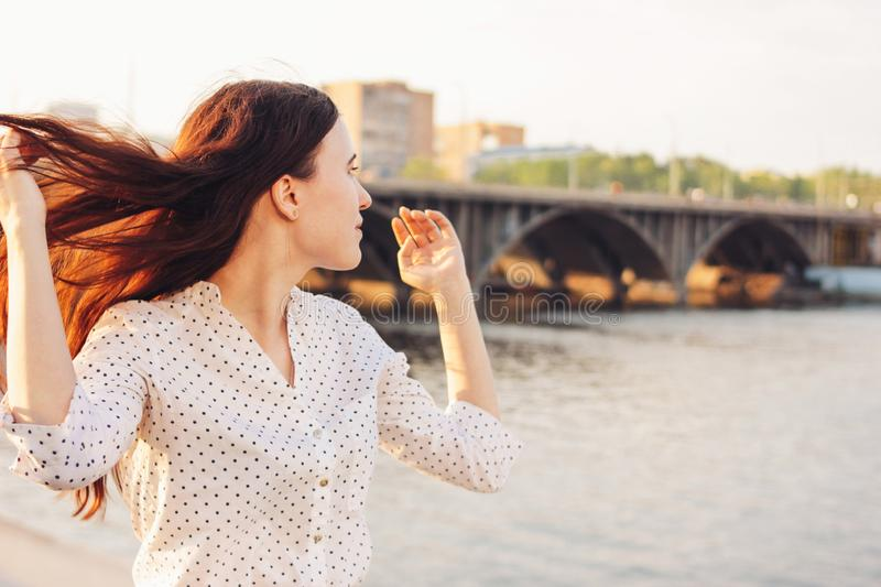 Positive beautiful long hair happy girl in white shirt on city river bridge background, summer travel vacation time. Positive beautiful long hair happy girl in stock photos