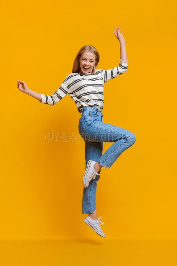 Positive beautiful teen girl jumping in air with hands up stock photo