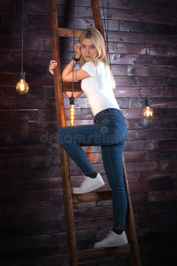 Positive beautiful young woman in jeans and white t-shirt on a wooden ladder on the background of a stylish dark wood wall. Wooden stock photography