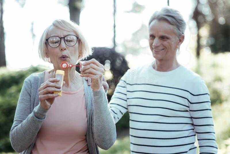 Positive begeisterte Frau, die Blasen macht stockfotografie