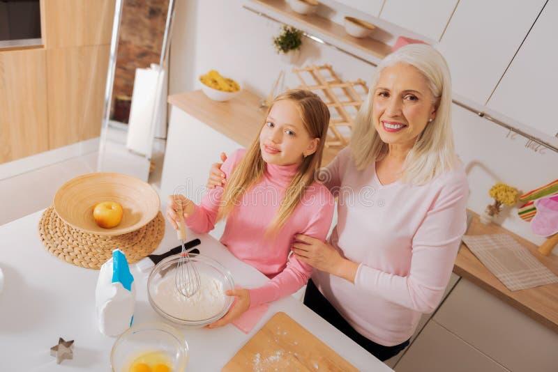 Positive begeisterte Großmutter und Enkelin, die in der Küche steht stockfoto
