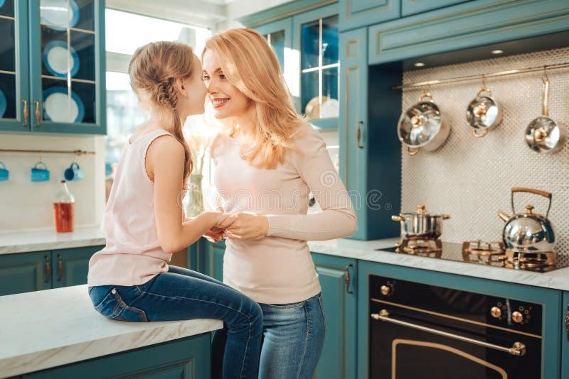 Positive begeisterte junge Mutter, die mit Kind sich verständigt stockbilder