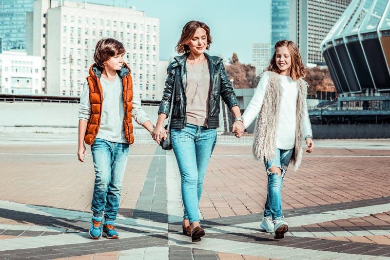 Positive begeisterte Kinder, die Feiertage mit Mutter verbringen stockfotos