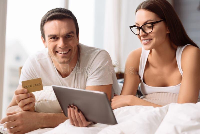 Positive begeisterte Paare, die online kaufen stockfoto