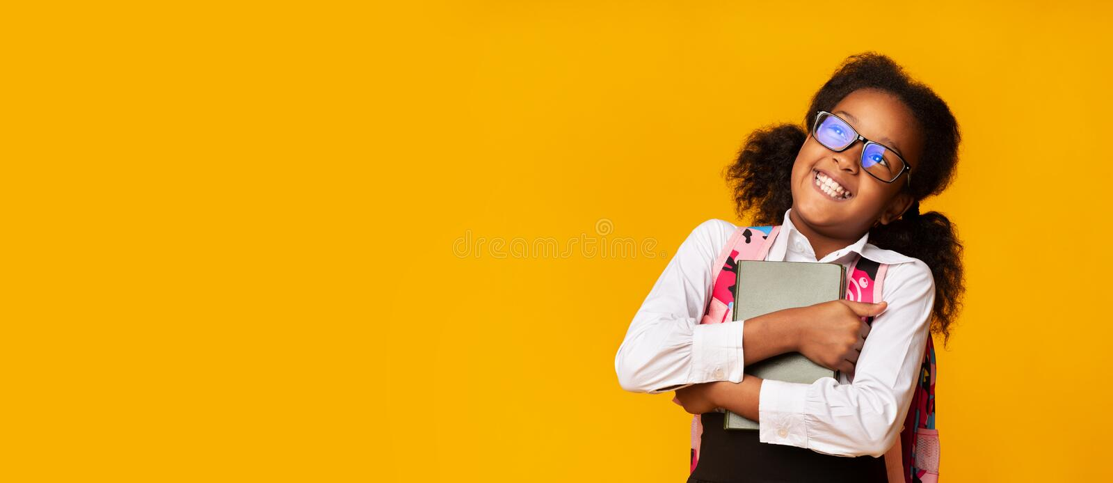 Positive Black Schoolgirl Embracing Book, Studio Shot, Panorama. Positive Black Schoolgirl Embracing Book On Yellow Background. Happy Back To School. Free Space stock images