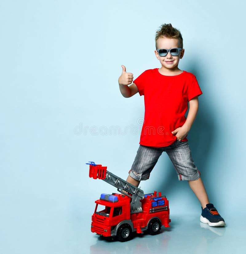 Positive blond boy in bright stylish casual clothing, sneakers, sunglasses standing near toy fire engine and showing thumb sign royalty free stock images