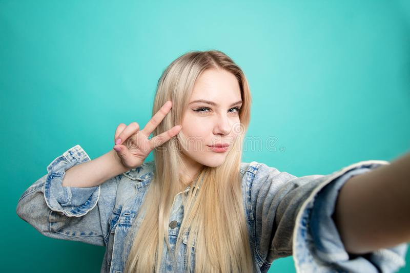Positive blond-haired woman taking selfie on blue background making fun with herself. Attractive blond woman taking selfie showing Peace sign with fingers on royalty free stock photos