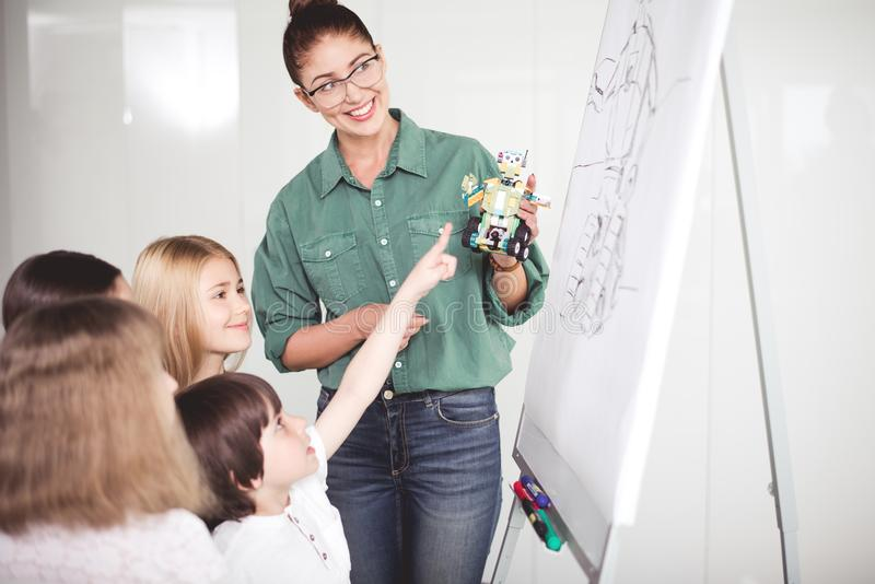 Outgoing woman and satisfied kids during lesson stock image