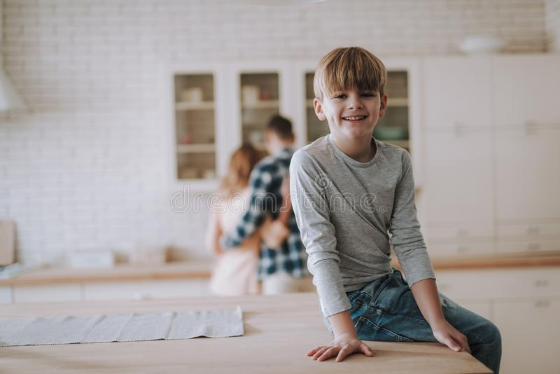 Positive boy sitting on the table in the kitchen and smiling stock photos