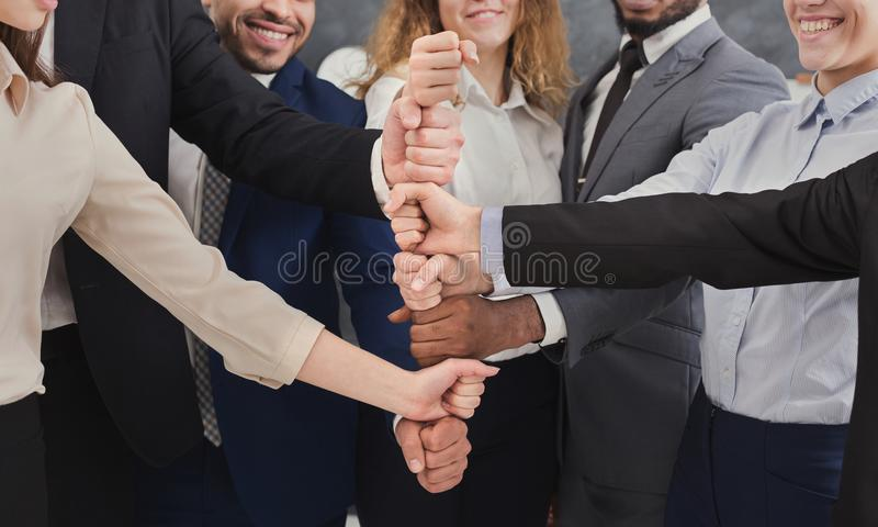 Positive business people putting fists on top of each other stock photography