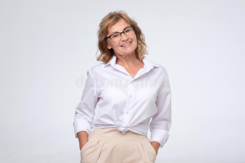 Positive business woman of middle age posing over white with arms crossed, copy cpace stock photo