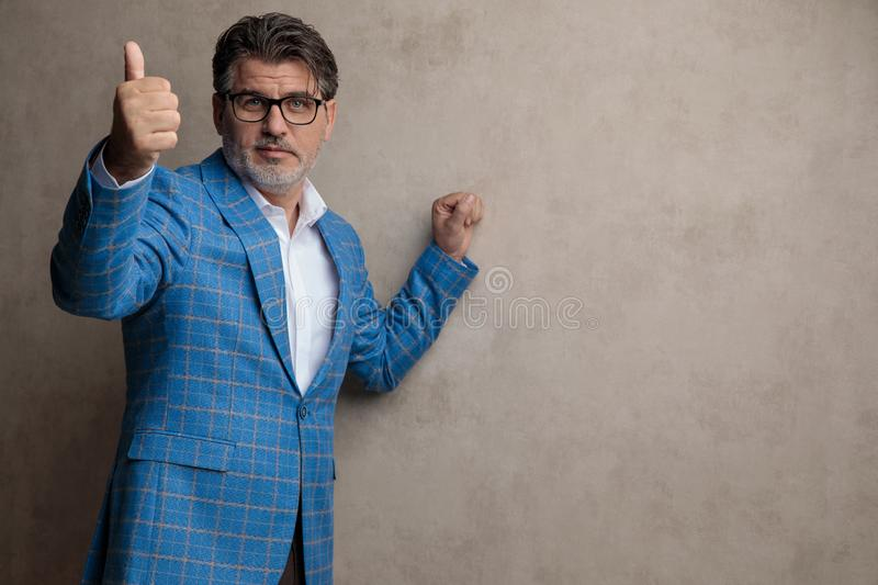 Positive businessman giving a thumb up and looking forward stock image