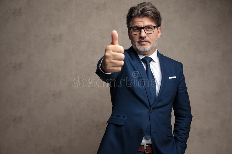 Positive businessman giving a thumb up royalty free stock images