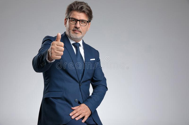 Positive businessman giving a thumbs up royalty free stock photography