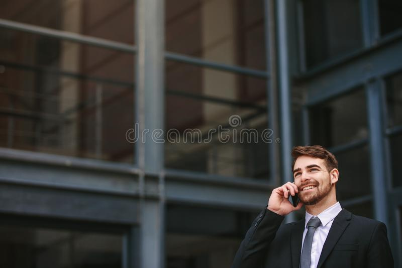 Positive businessman outdoors talking on phone stock photos